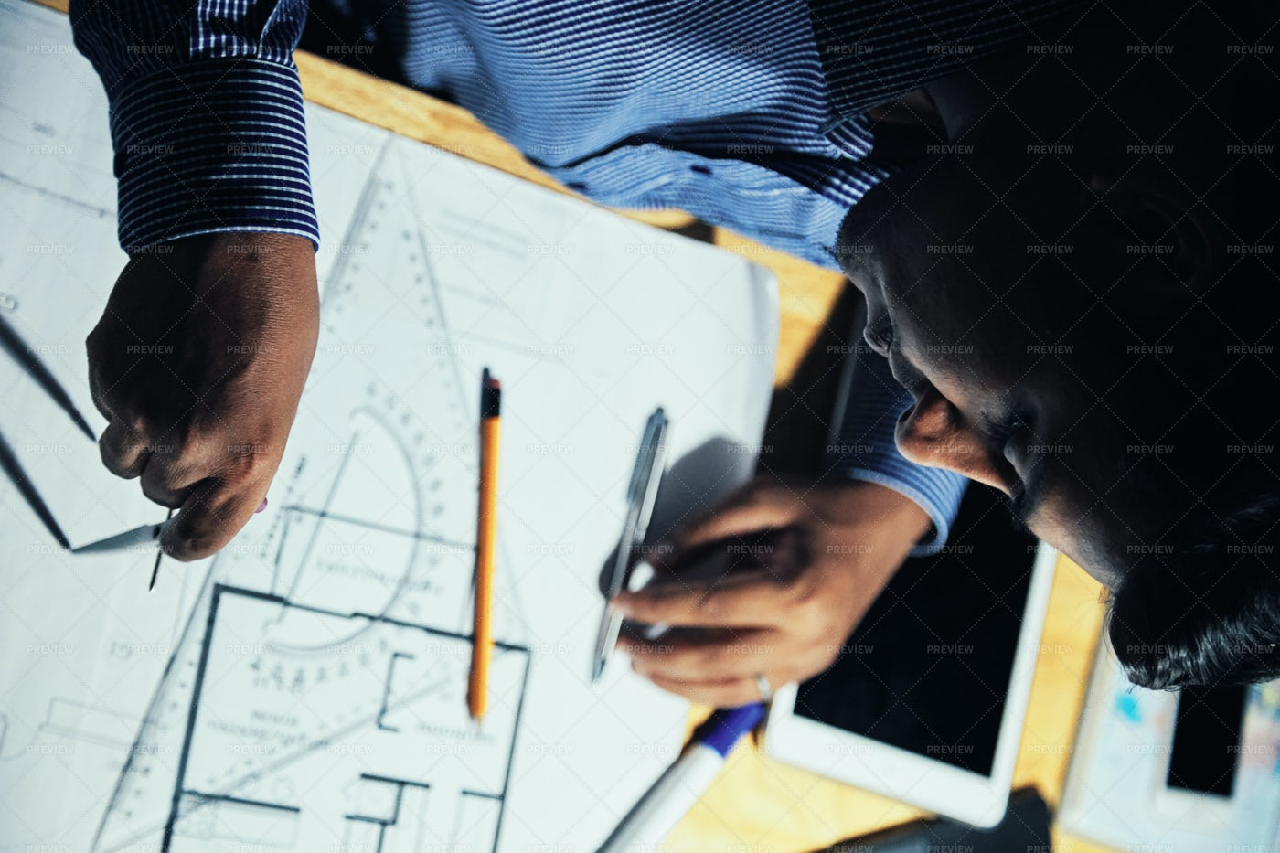 Man Working On Blueprint In Evening: Stock Photos