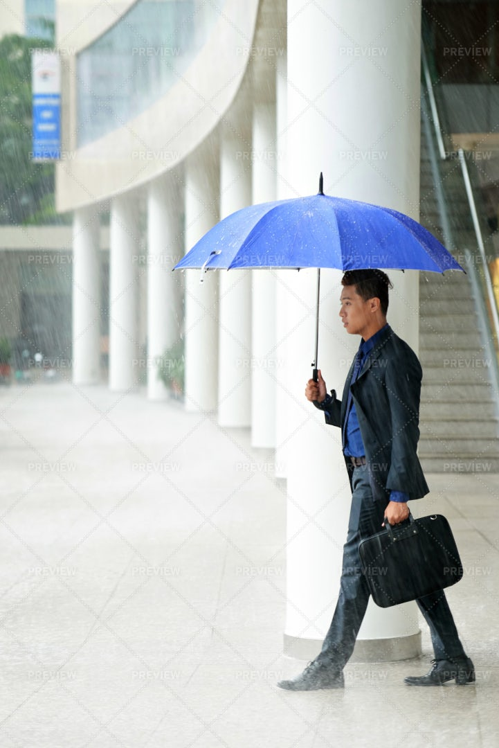 Asian Manager In Pouring Rain: Stock Photos
