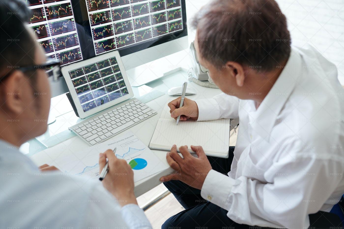 Brokers Analyzing Trends: Stock Photos