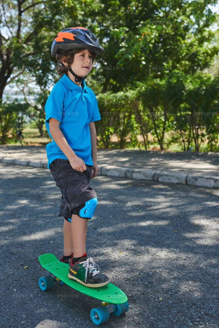 Curly Little Boy With Penny Board: Stock Photos