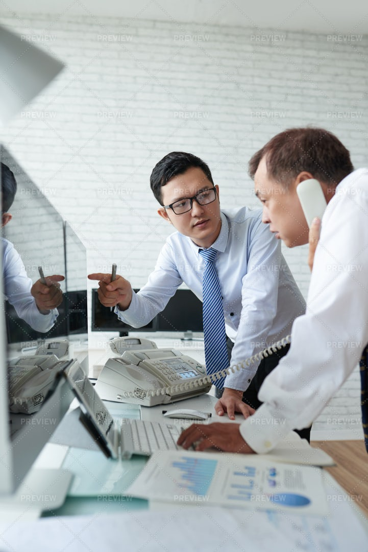 Brokers Discussing Financial Charts: Stock Photos