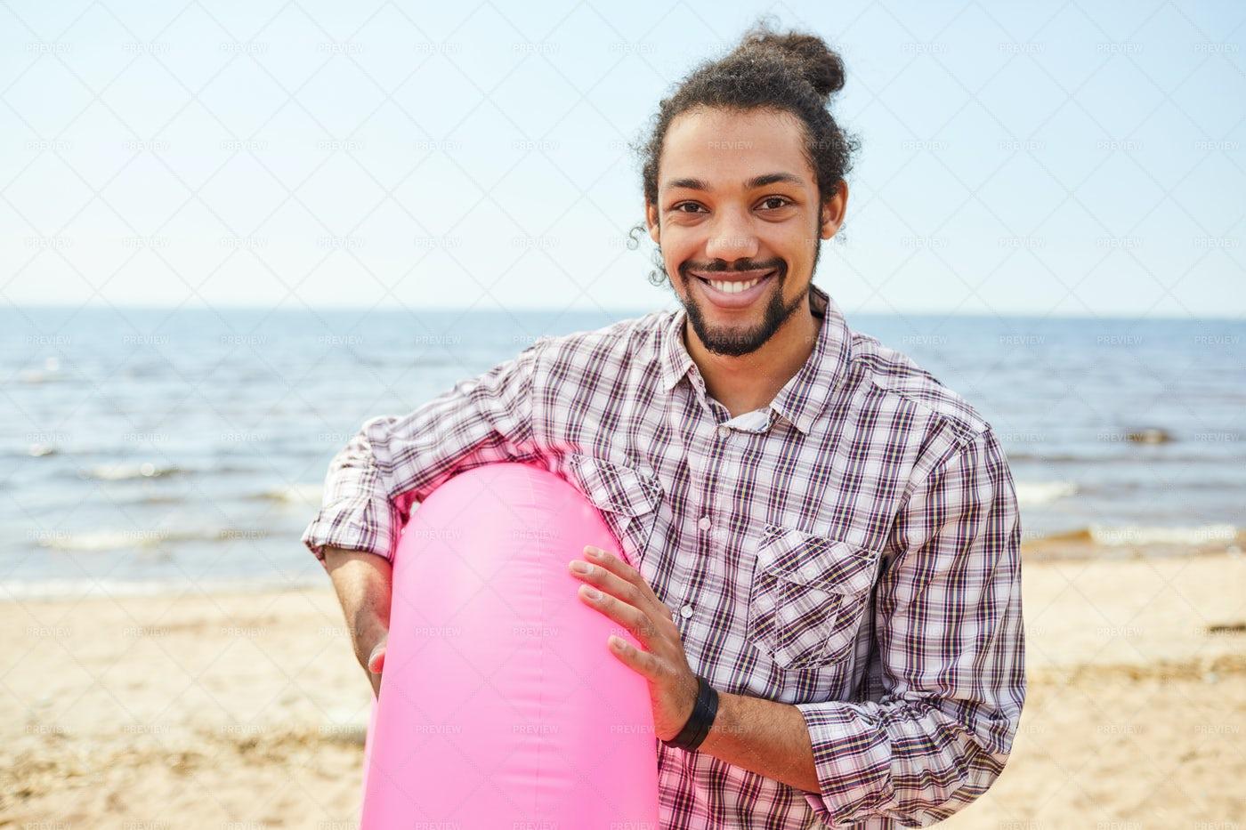 Mixed-Race Man Holding Swim Tube At...: Stock Photos