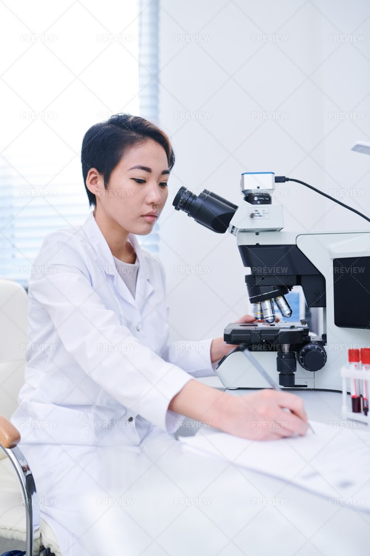 Asian Biologist Studying Cells With...: Stock Photos