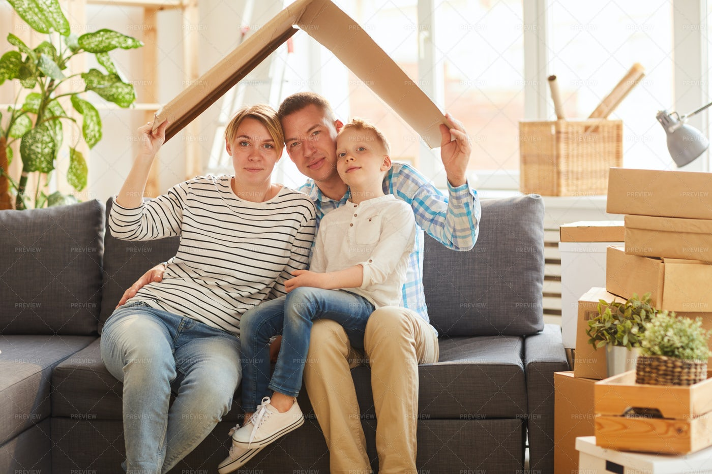 Family Holding Cardboard Roof Above...: Stock Photos