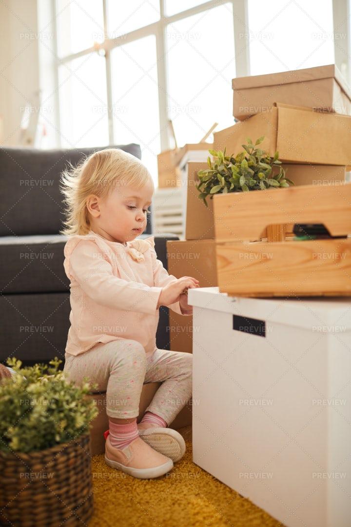 Curious Girl Opening Moving Box: Stock Photos
