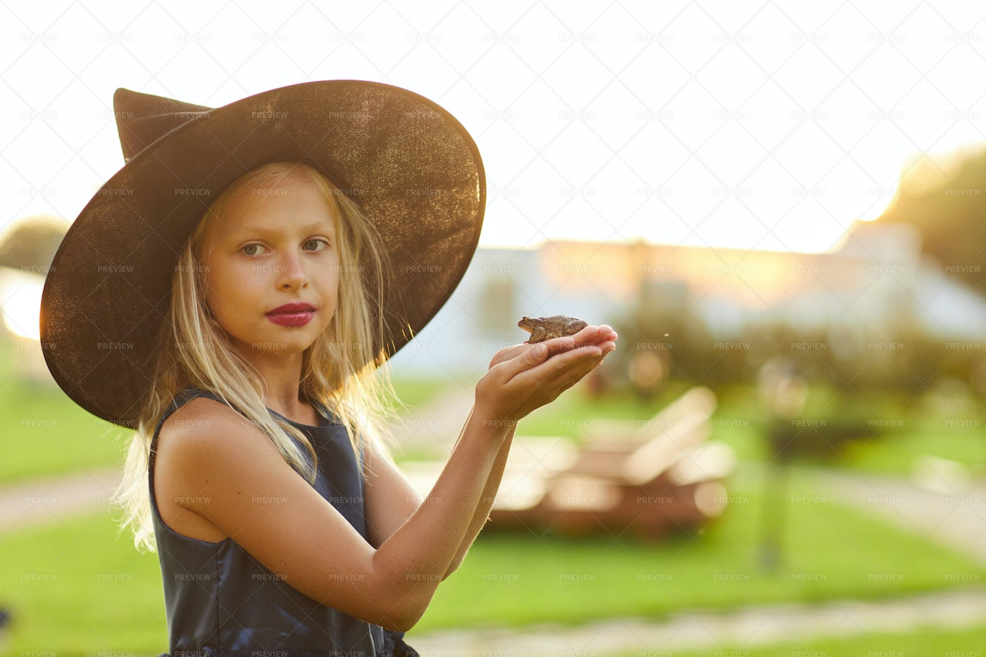 Cute Little Witch Holding Frog: Stock Photos