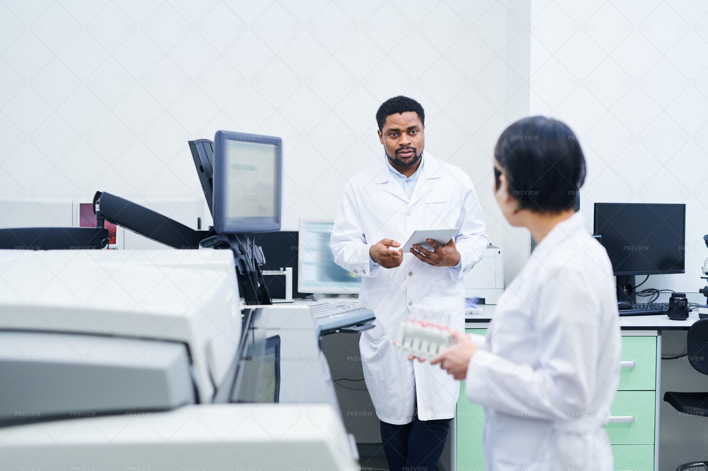 Black Doctor Talking To Colleague...: Stock Photos