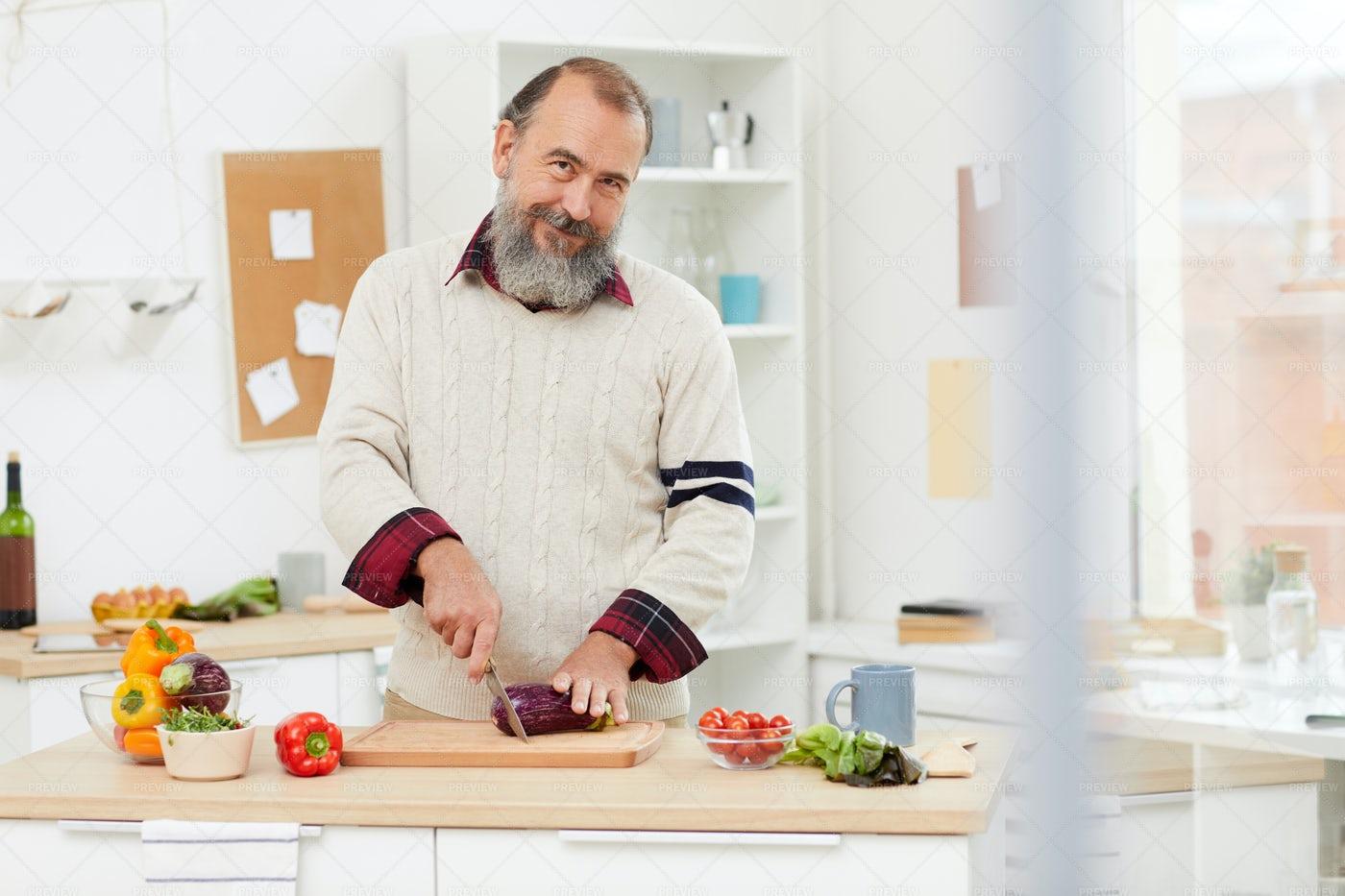 Smiling Senior Man Cooking In...: Stock Photos