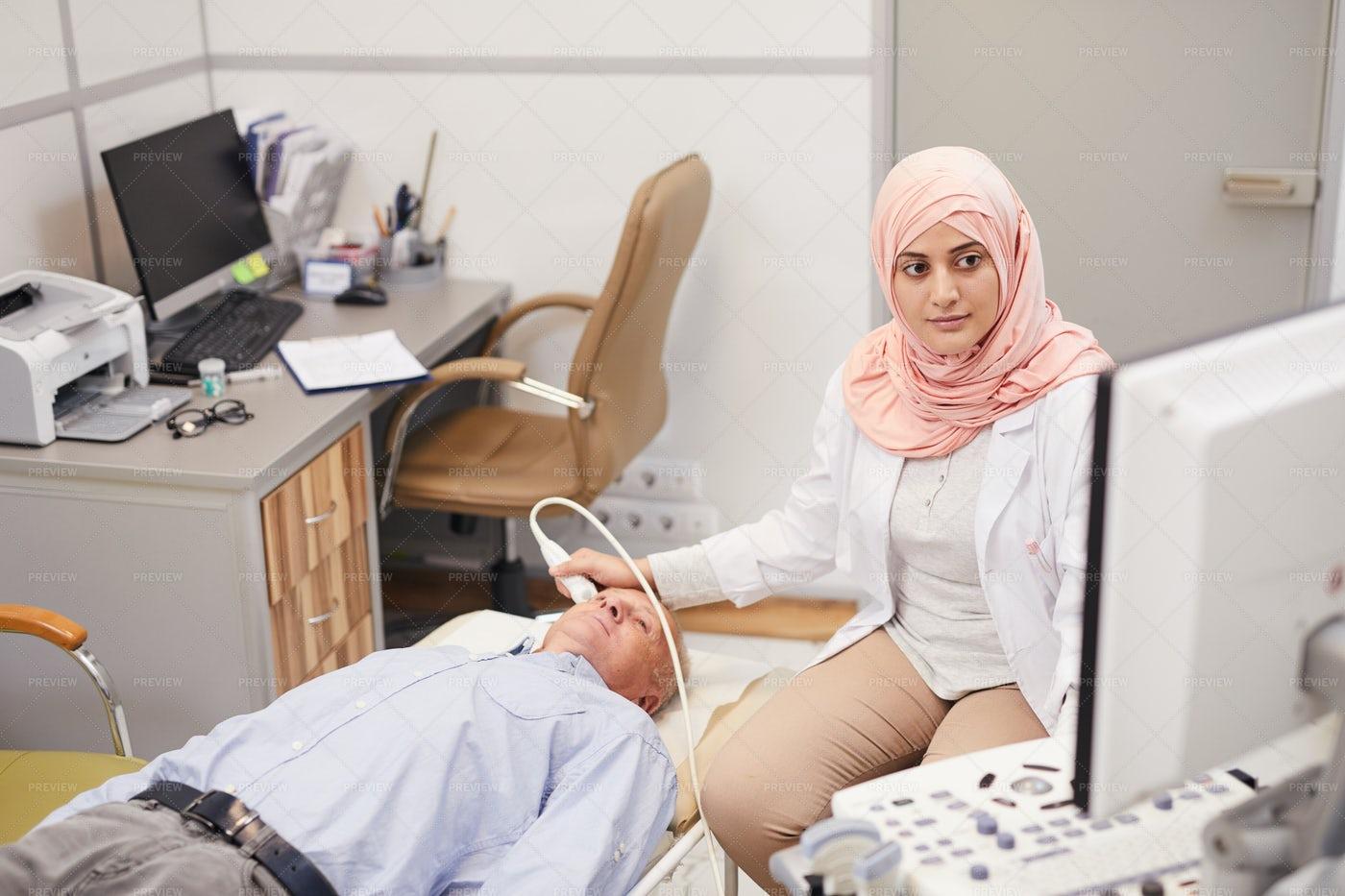 Arab Female Nurse Examining Senior...: Stock Photos