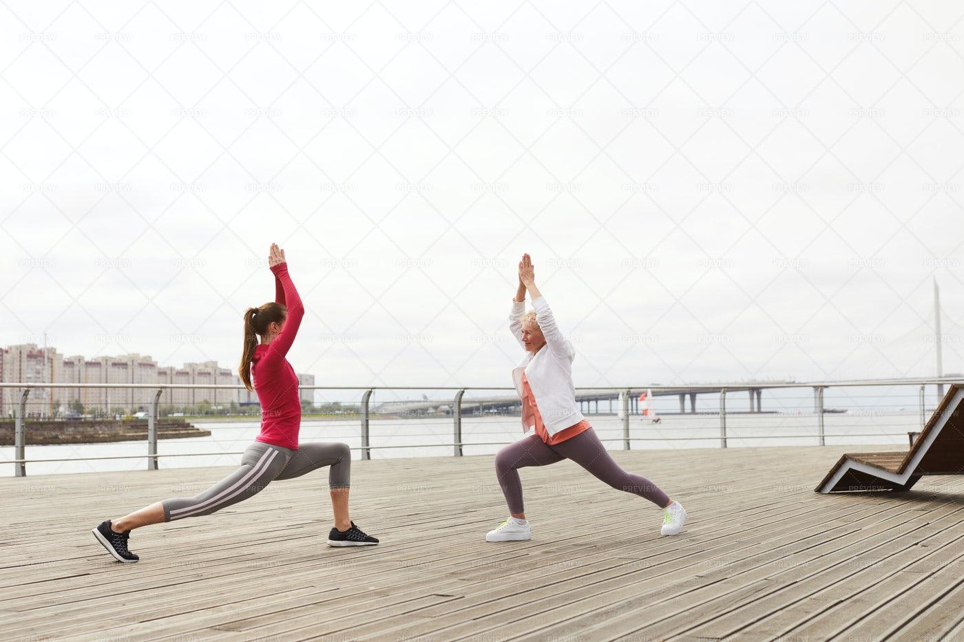 Two Women Doing Yoga On Pier: Stock Photos