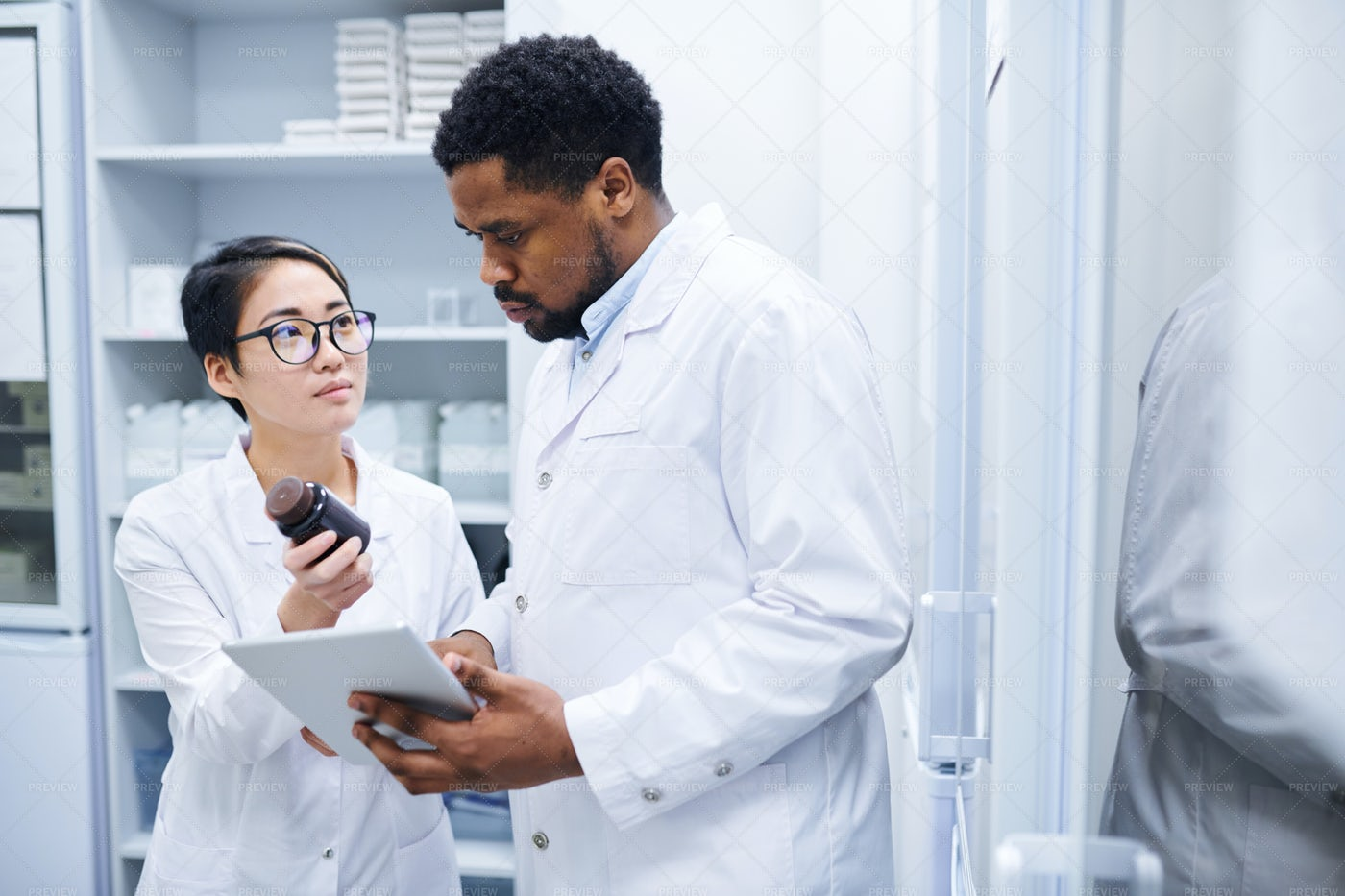 Medical Assistant Asking Doctor...: Stock Photos