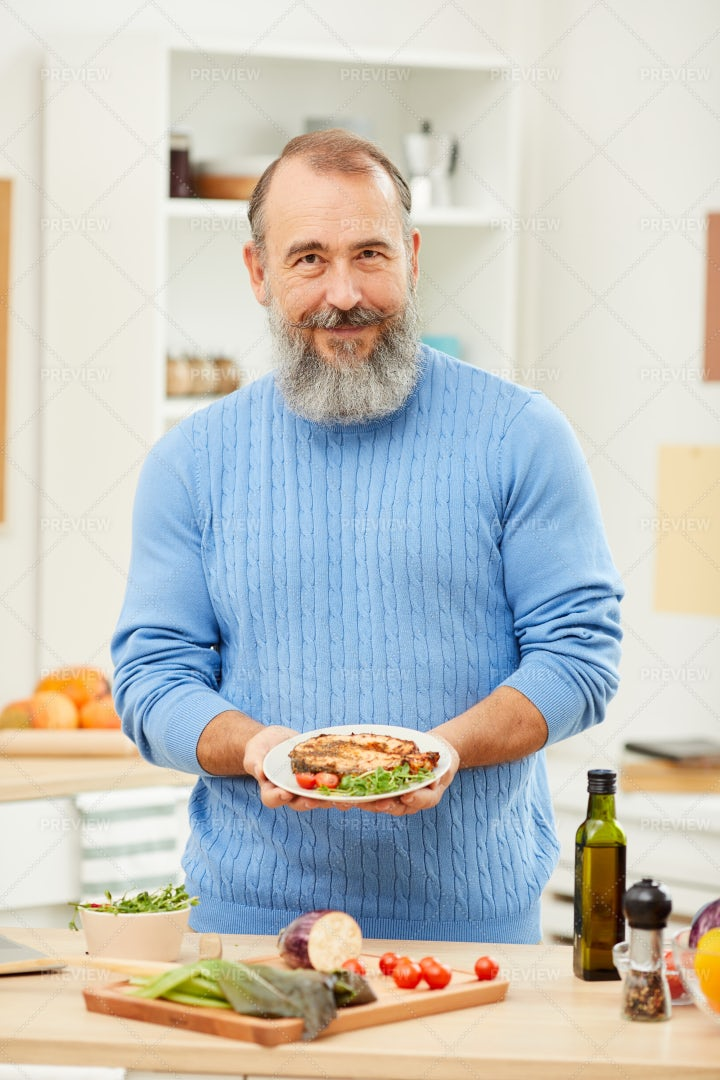 Senior Man Presenting Homemade Dish: Stock Photos