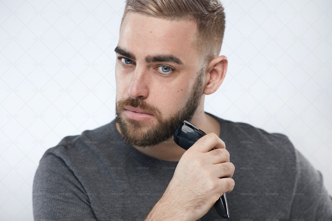 Young Man Trimming Beard: Stock Photos
