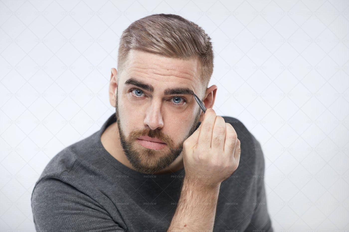 Caucasian Man Tweezing Eyebrows: Stock Photos