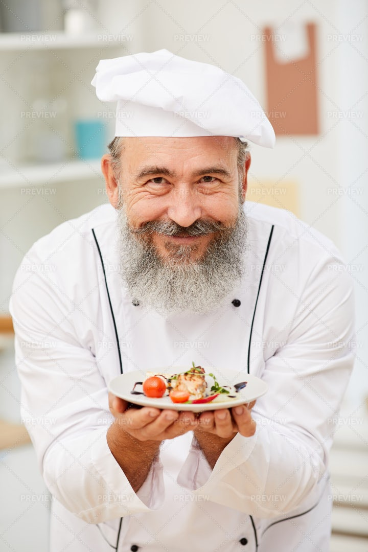 Smiling Senior Chef Presenting Dish: Stock Photos