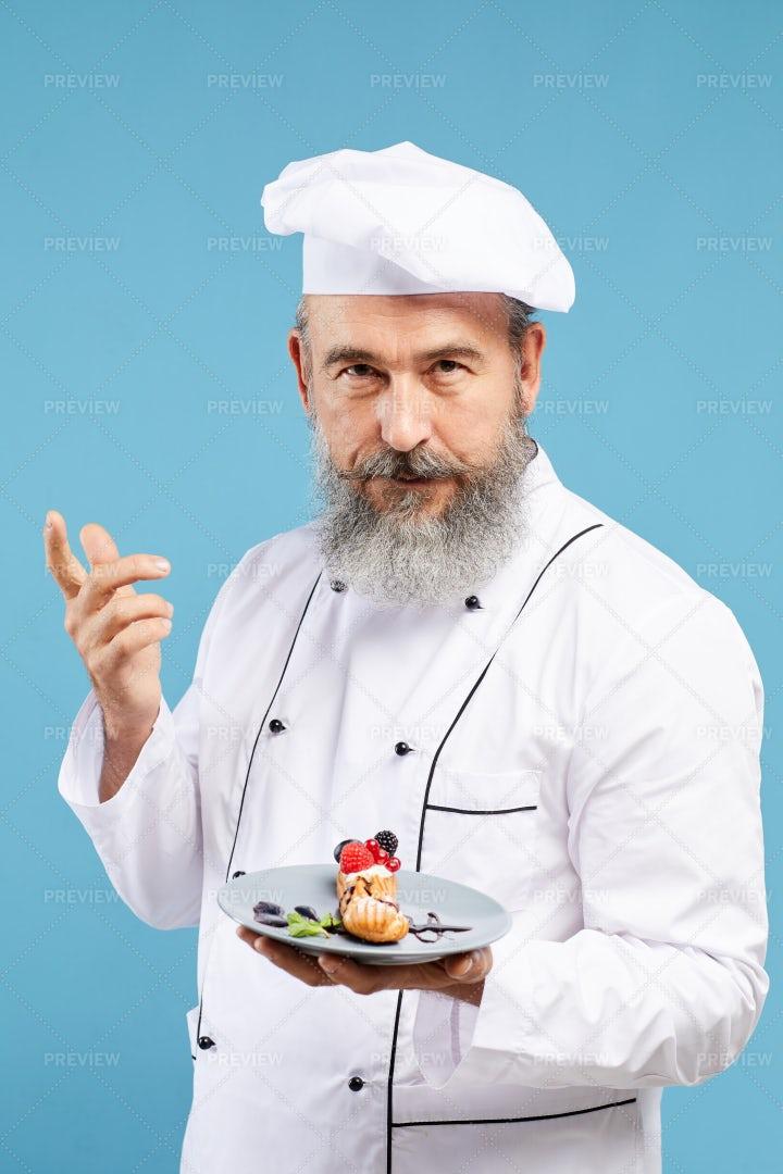Senior Chef Presenting Dessert On...: Stock Photos