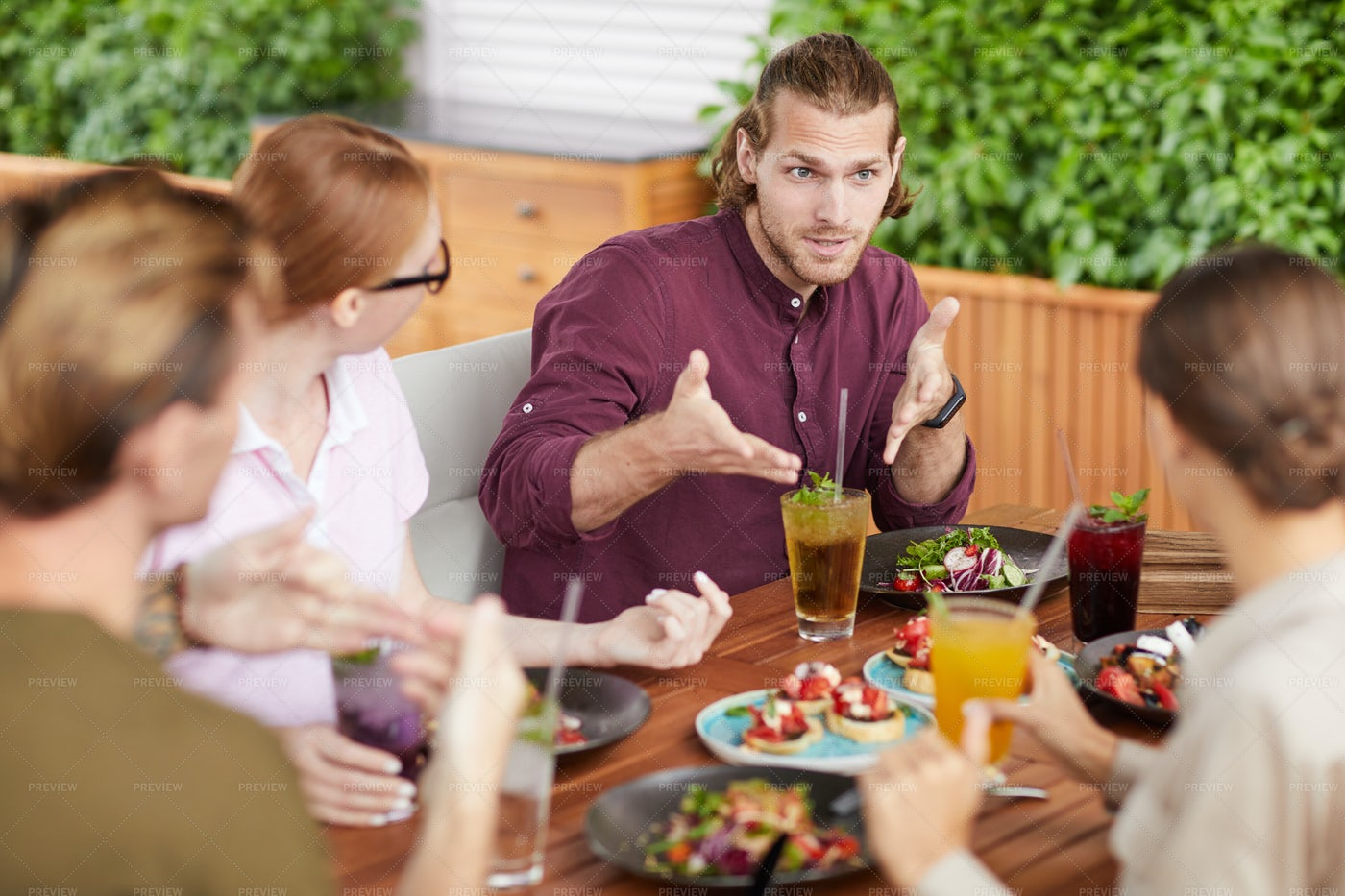 Friends Chatting During Lunch In...: Stock Photos