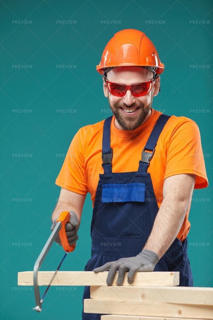 Joyful Carpenter Sawing Wooden...: Stock Photos