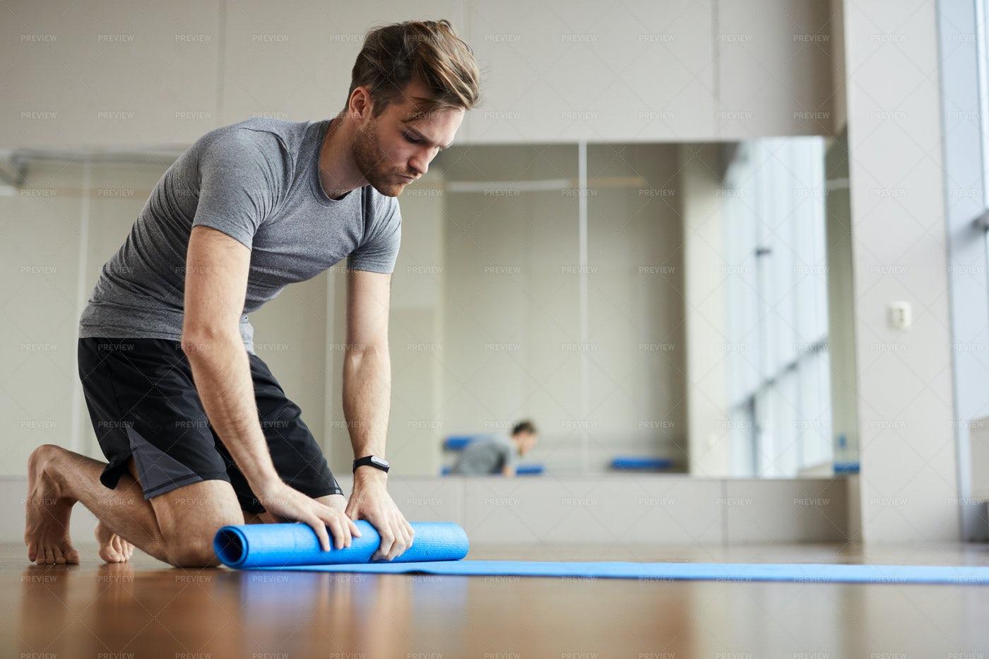 Young Man Packing Yoga Mat: Stock Photos