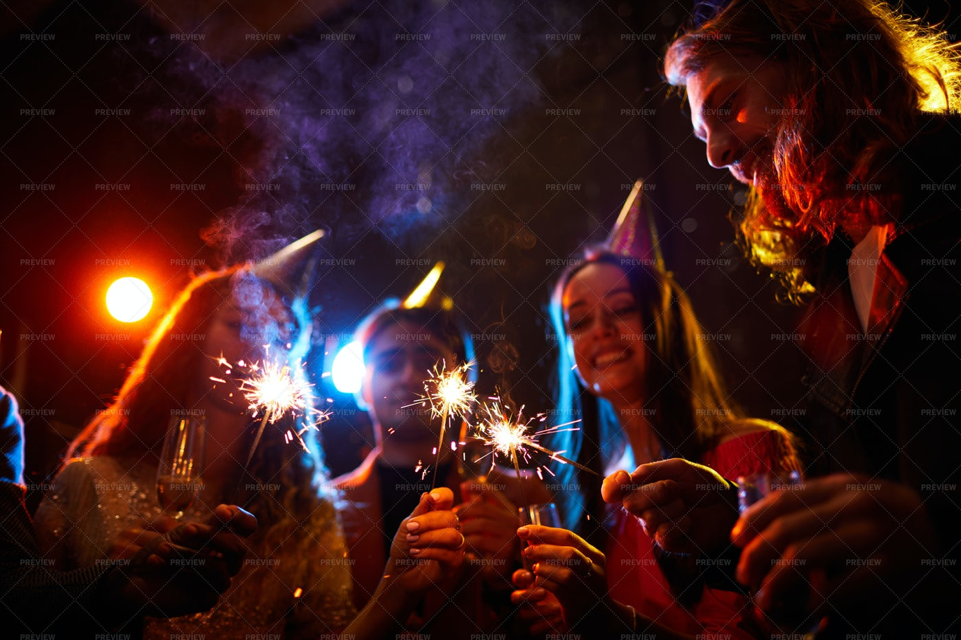Friends Lighting Sparklers At...: Stock Photos