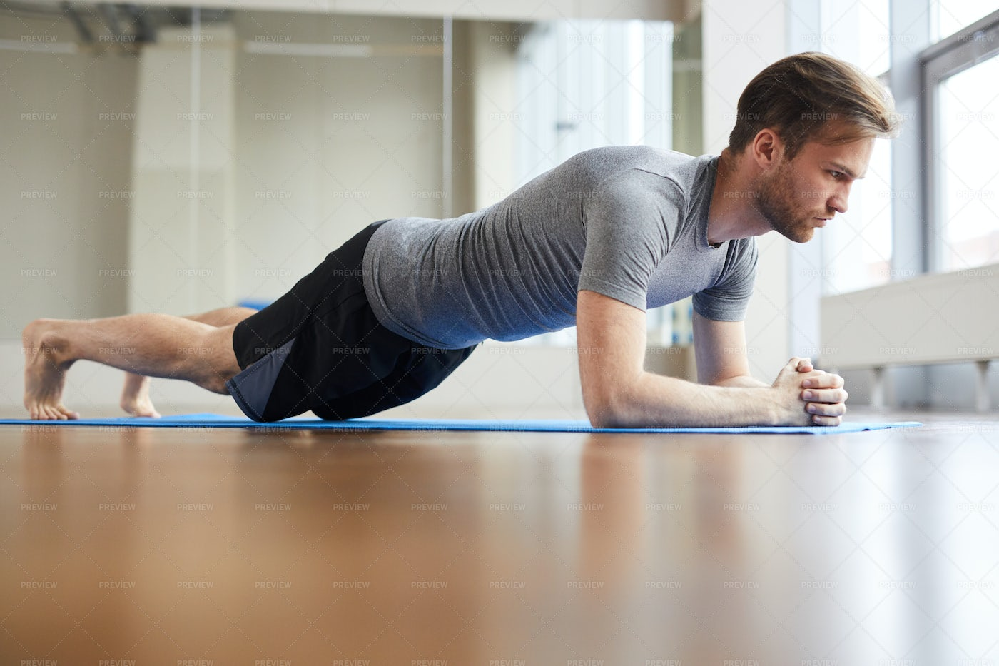Concentrated Man Doing Plank Pose: Stock Photos