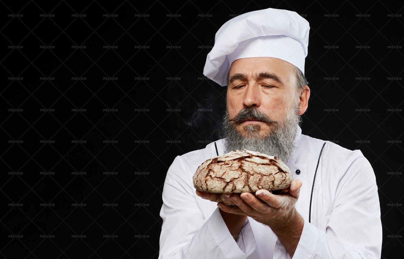 Bearded Baker Holding Fresh Loaf: Stock Photos