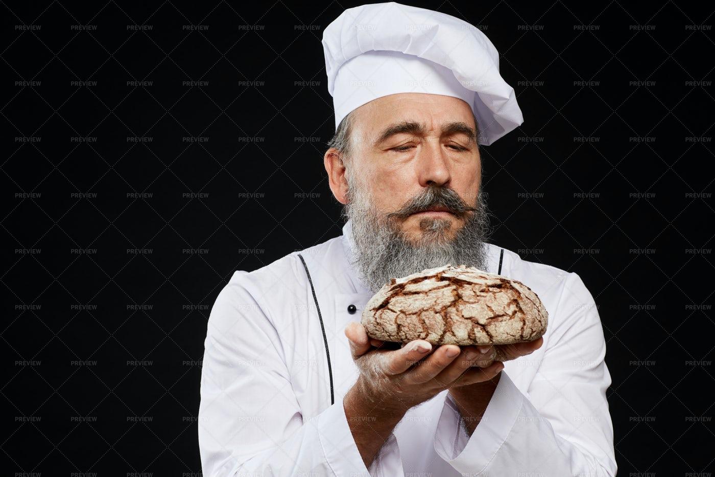 Bearded Baker Holding Fresh Bread: Stock Photos