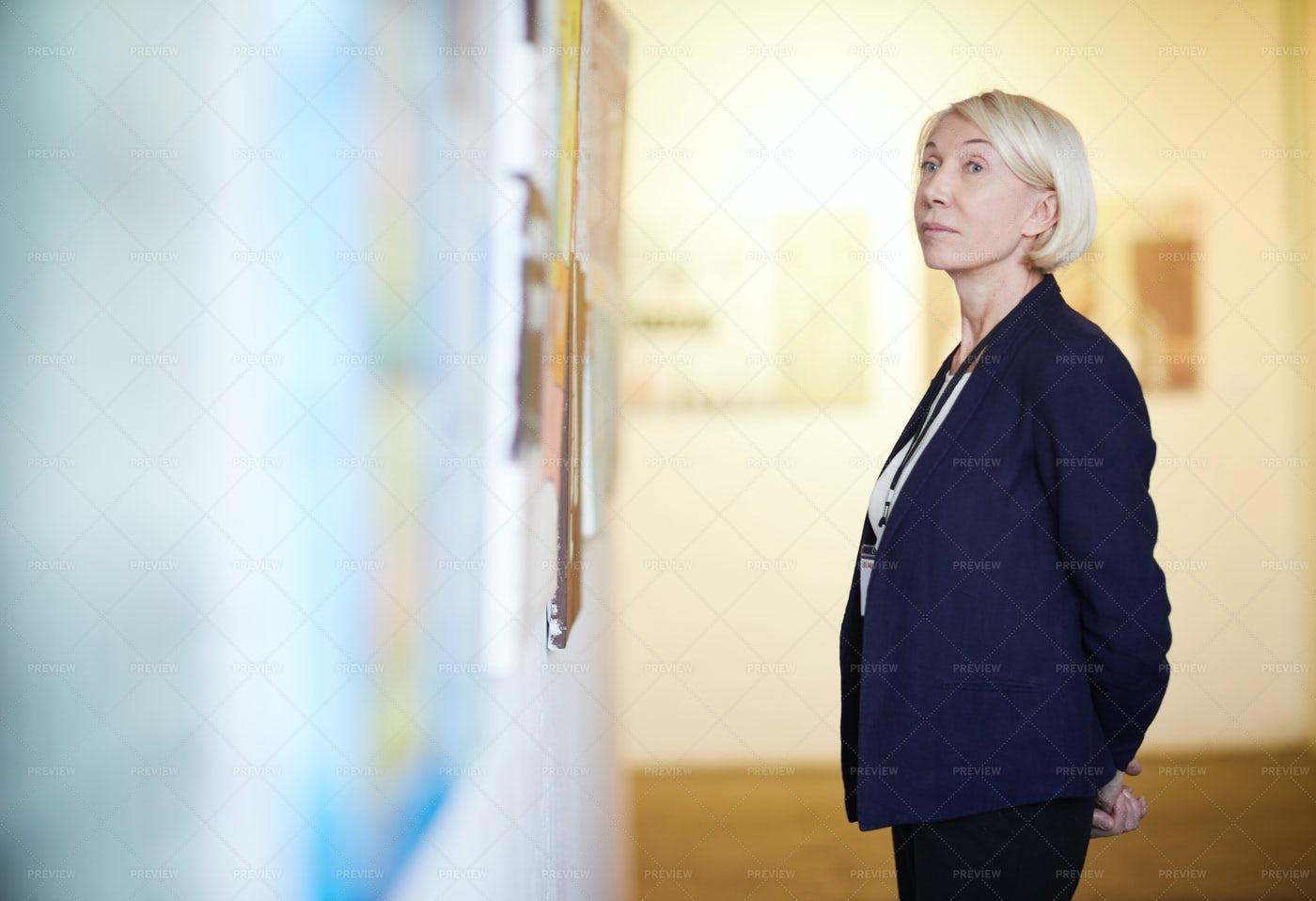 Mature Woman Looking At Paintings: Stock Photos