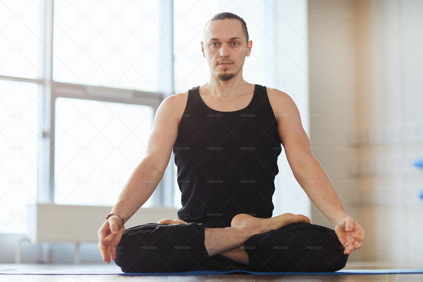Muscled Young Man Meditating Alone: Stock Photos