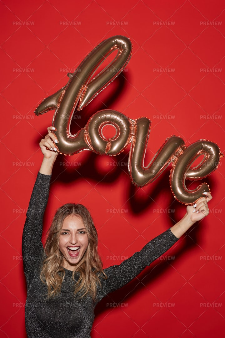 Cheerful Young Woman Holding Love...: Stock Photos