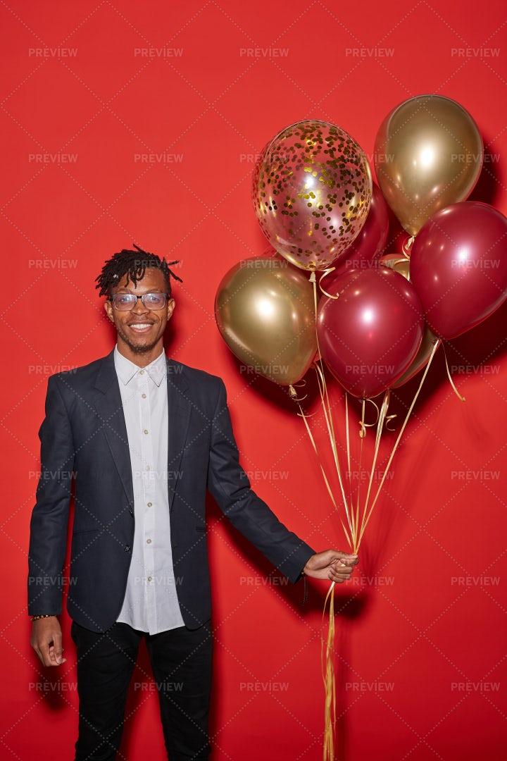 Trendy African Man Holding Balloons...: Stock Photos