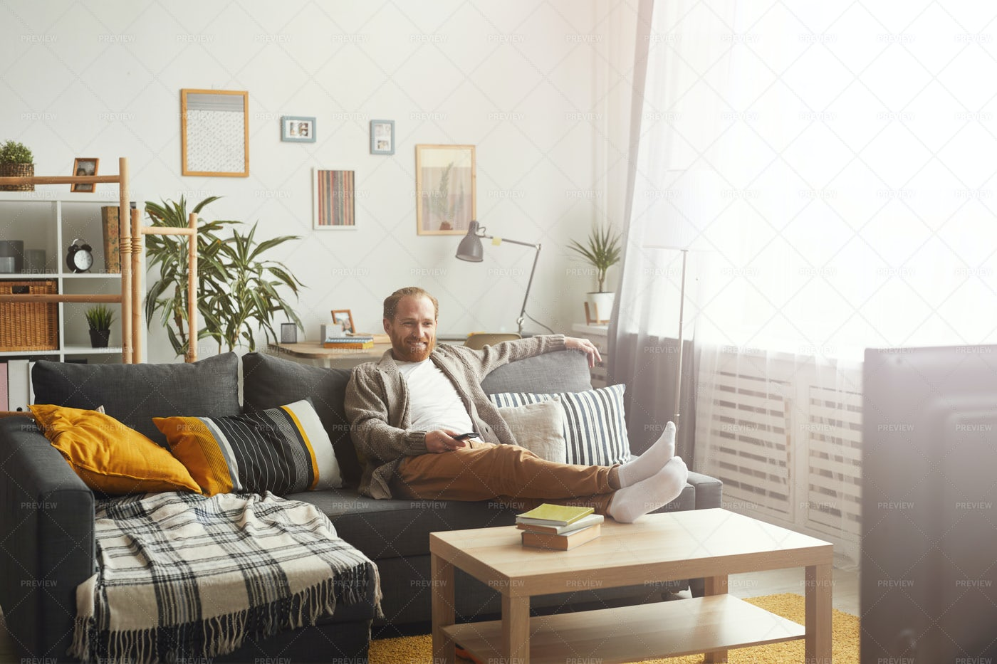 Smiling Man Watching TV At Home: Stock Photos