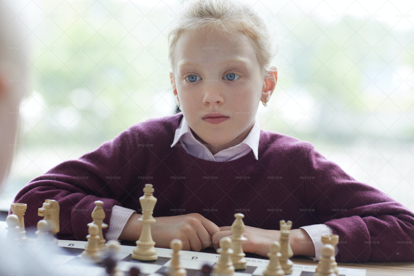 Blue-eyed Girl Playing Chess: Stock Photos
