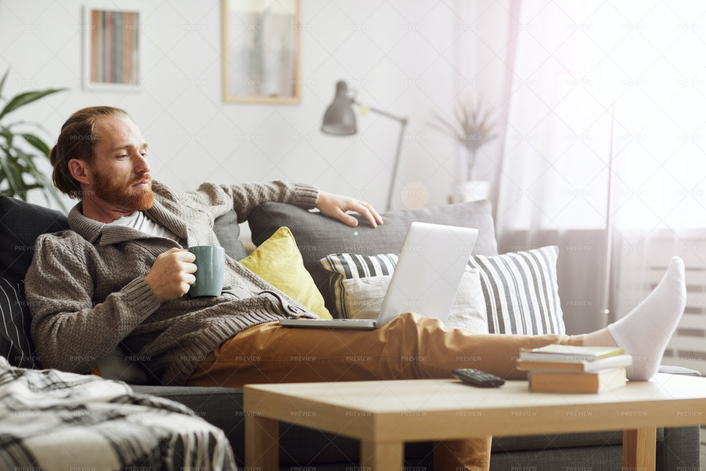 Bored Man Watching Videos Via...: Stock Photos