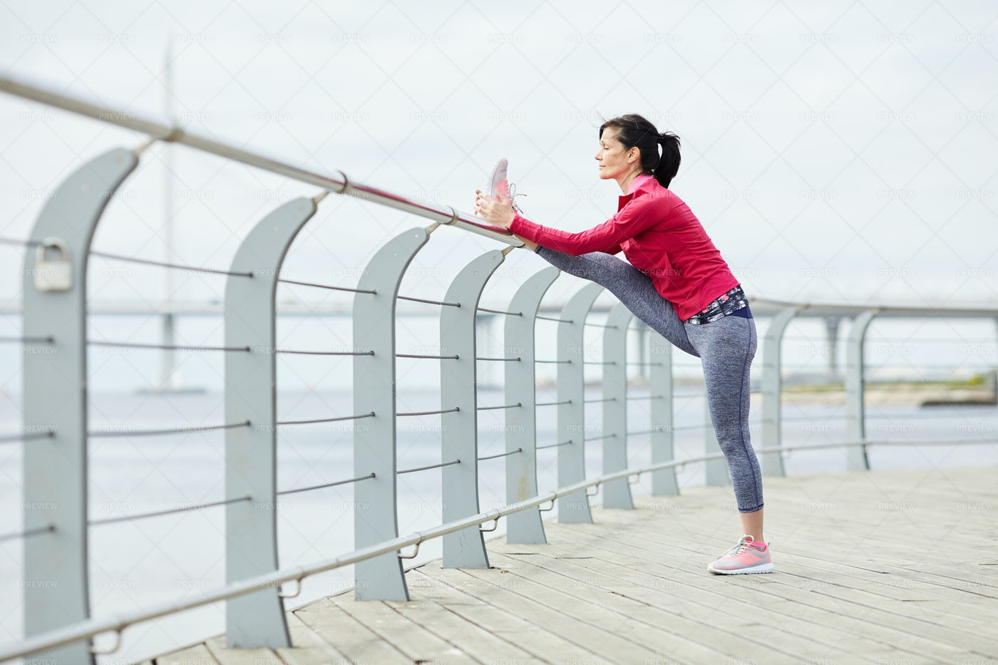 Active Woman Stretching On Pier: Stock Photos