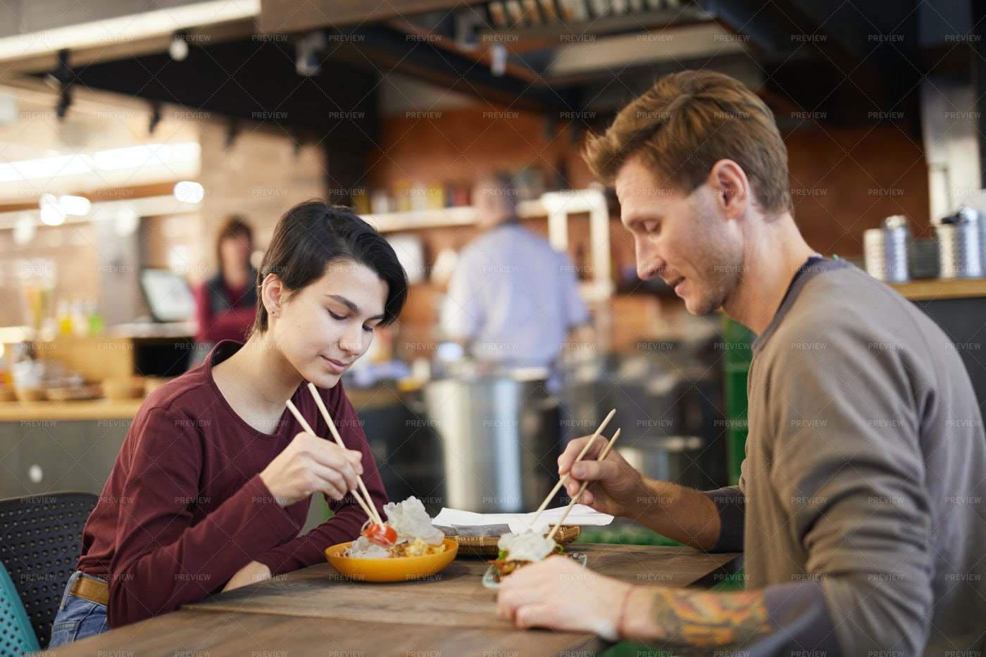 Couple Enjoying Asian Food In Cafe: Stock Photos