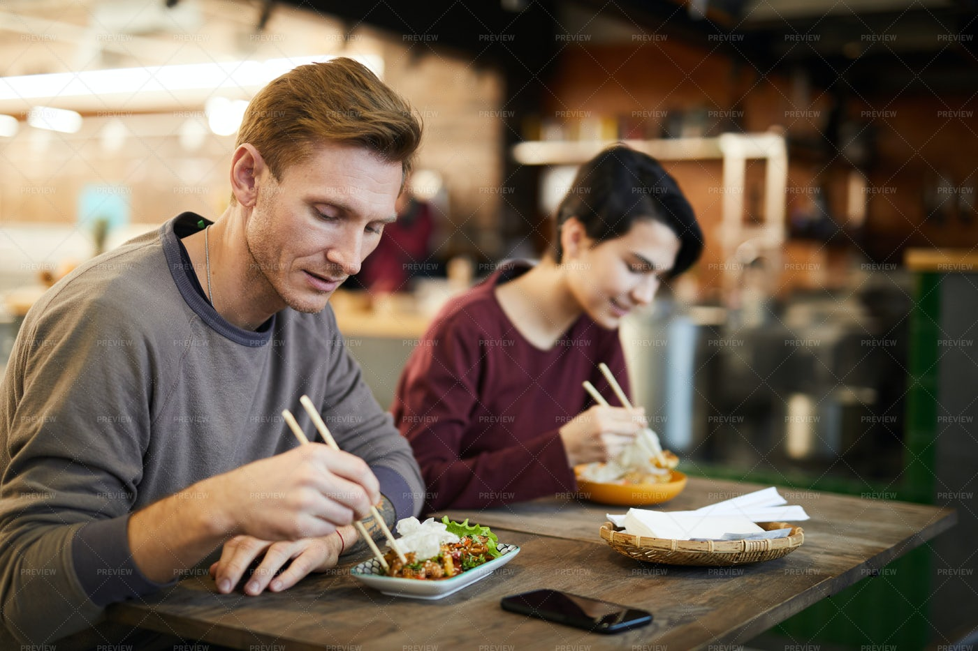 People Enjoying Asian Food In Cafe: Stock Photos