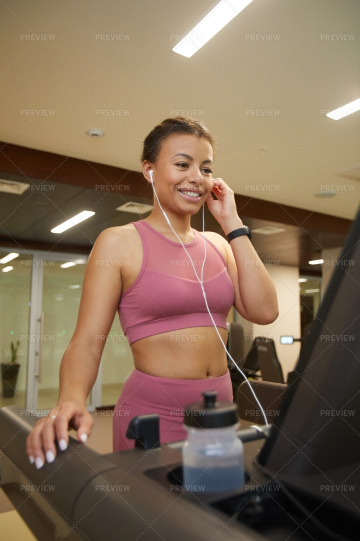 Smiling Woman Running On Treadmill: Stock Photos