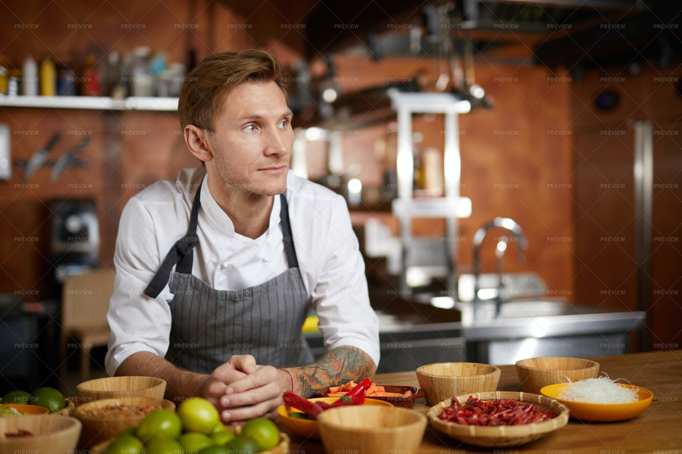 Tattooed Chef Posing In Kitchen: Stock Photos