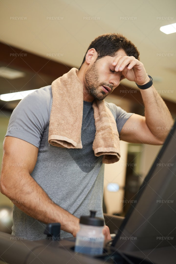 Exhausted Man Running On Treadmill: Stock Photos