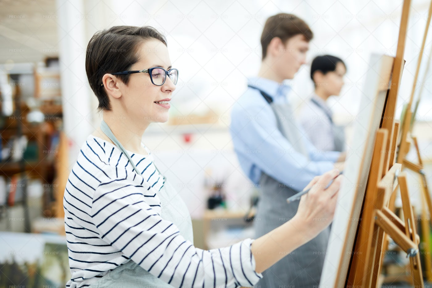 Woman Painting On Easel: Stock Photos