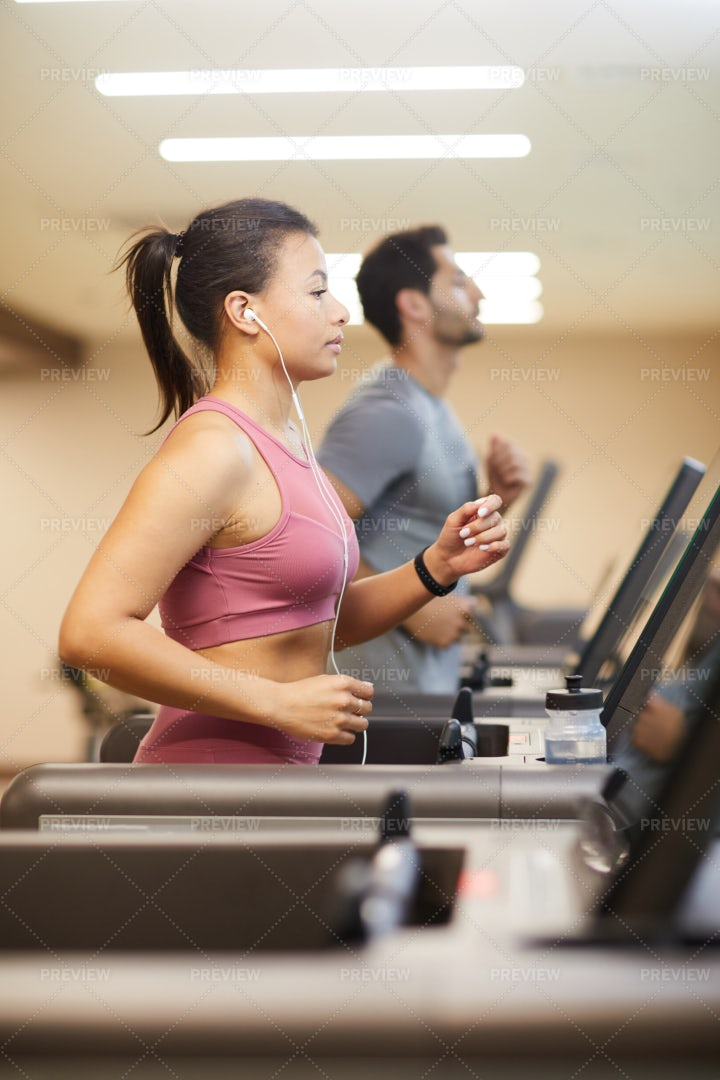 Two People Running On Treadmills In...: Stock Photos