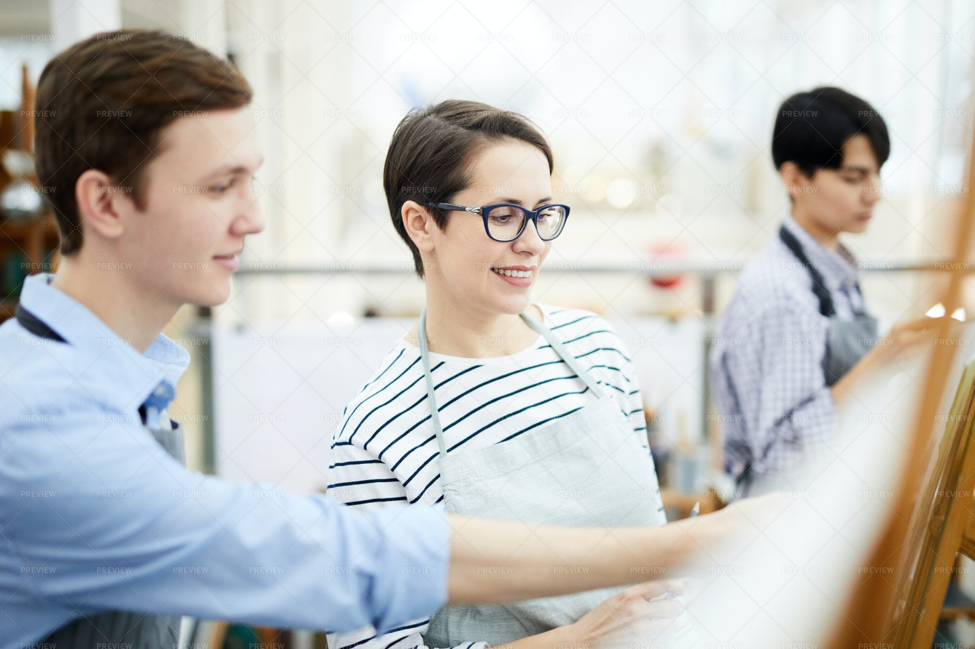 Smiling Woman Painting In Class: Stock Photos