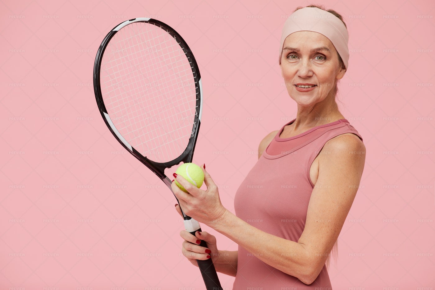 Mature Woman Playing Tennis Against...: Stock Photos