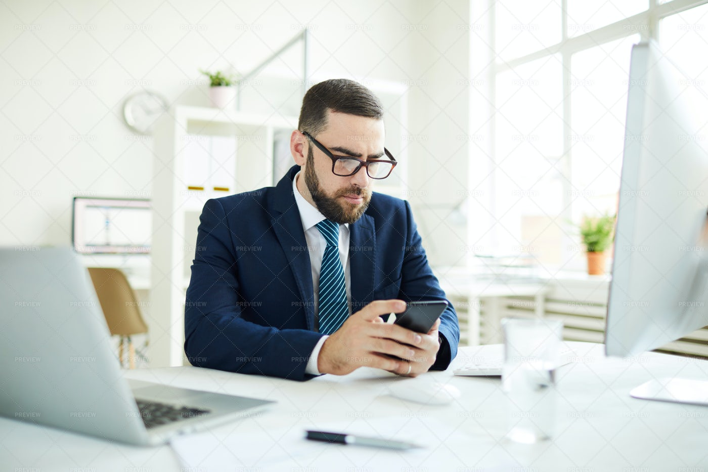 Businessman Reading Sms In Office: Stock Photos