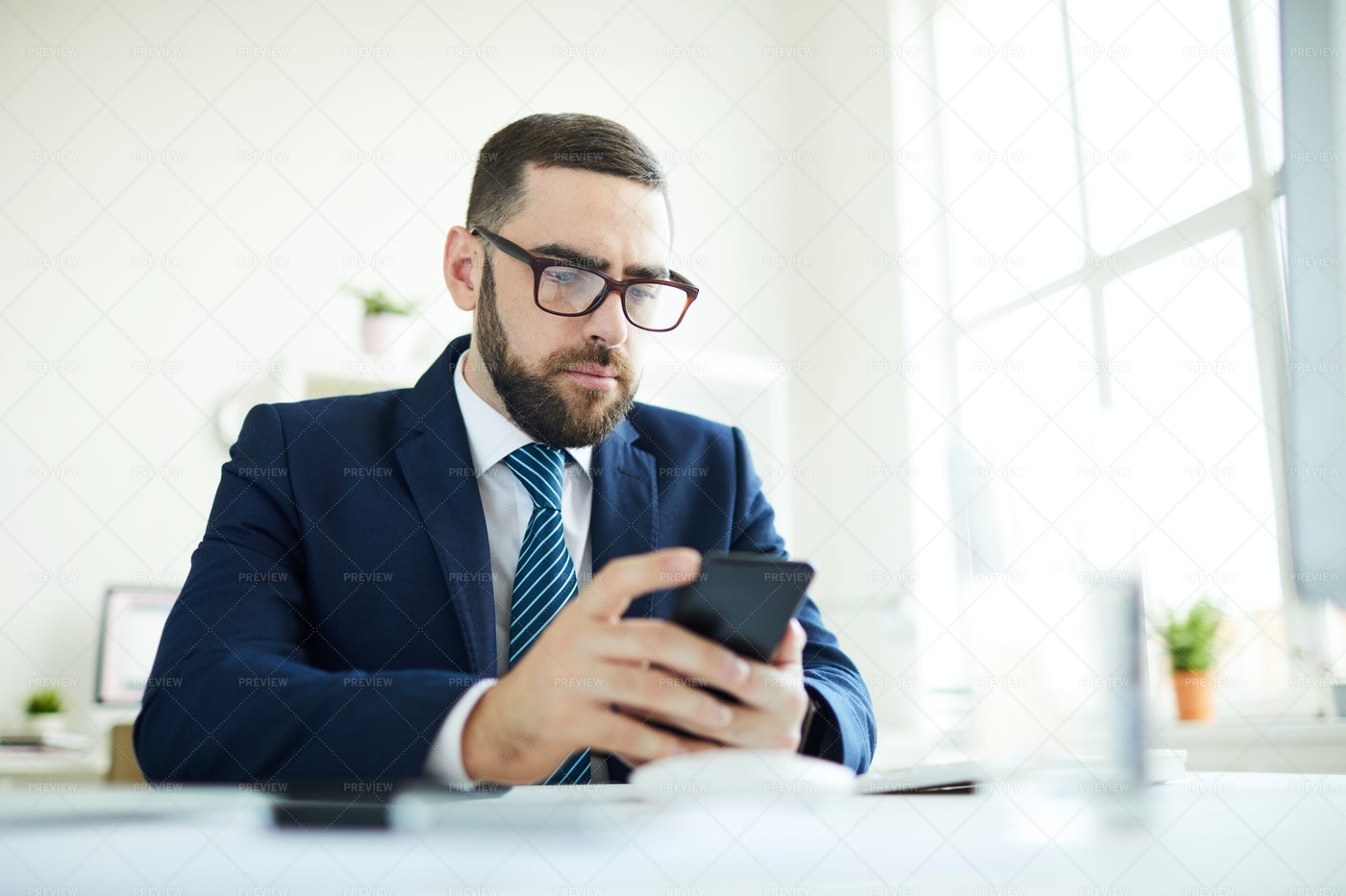 Business Manager Checking Phone In...: Stock Photos