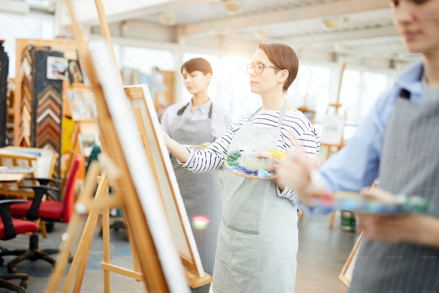 Row Of Artists In Sunlit Studio: Stock Photos