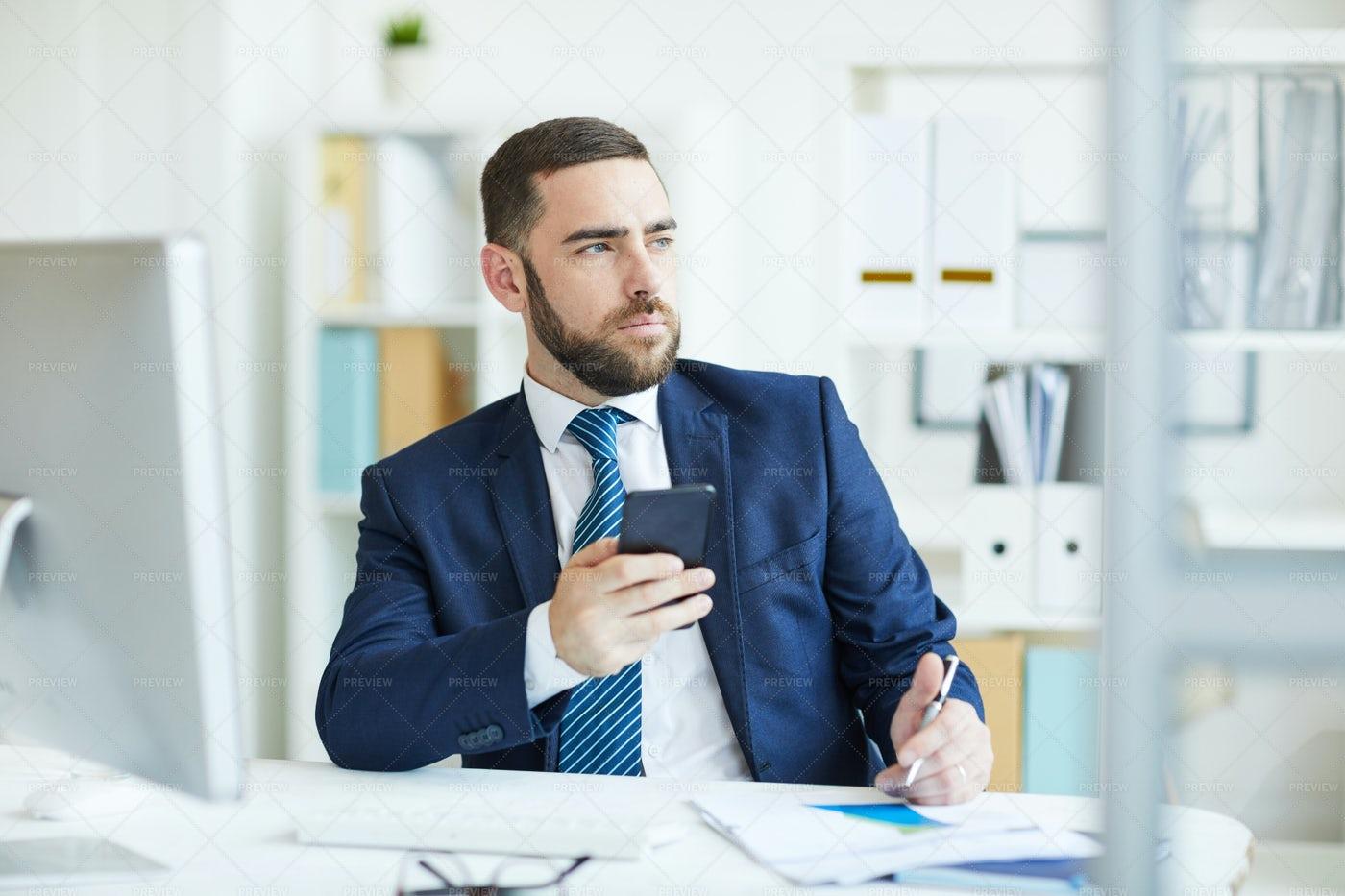 Pensive Businessman Checking Phone: Stock Photos