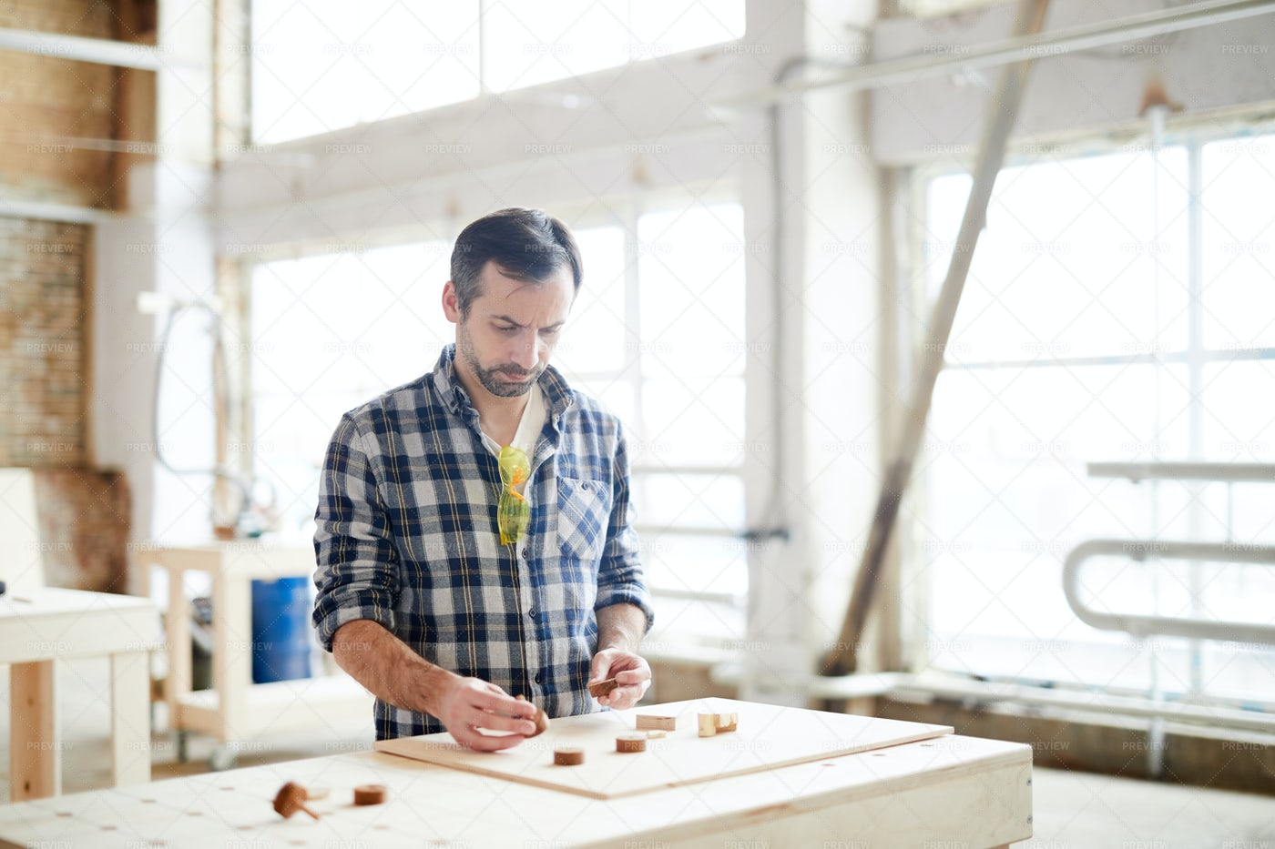 Busy Workman Comparing Small Wooden...: Stock Photos