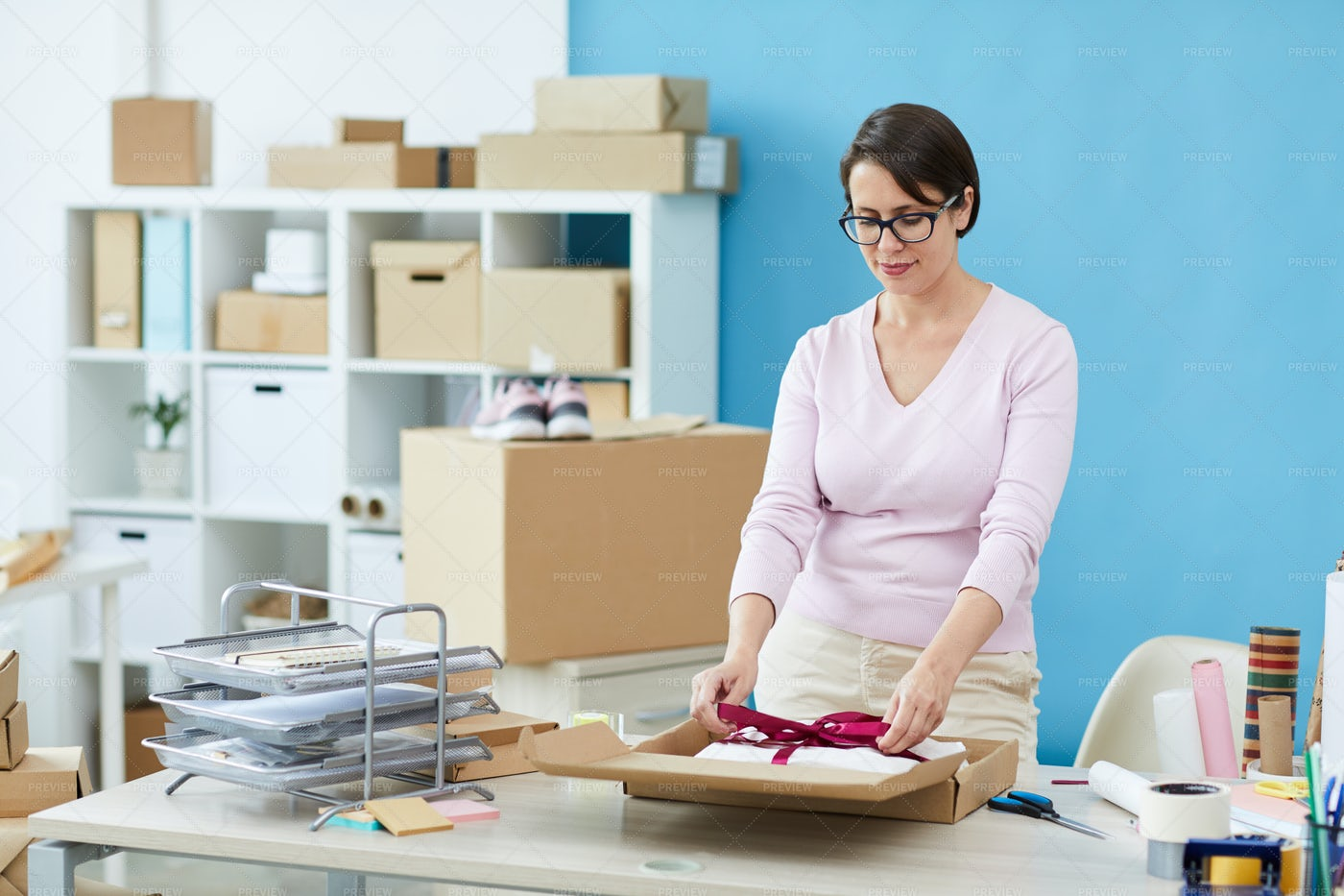 Casual Young Packing Manager Tying...: Stock Photos